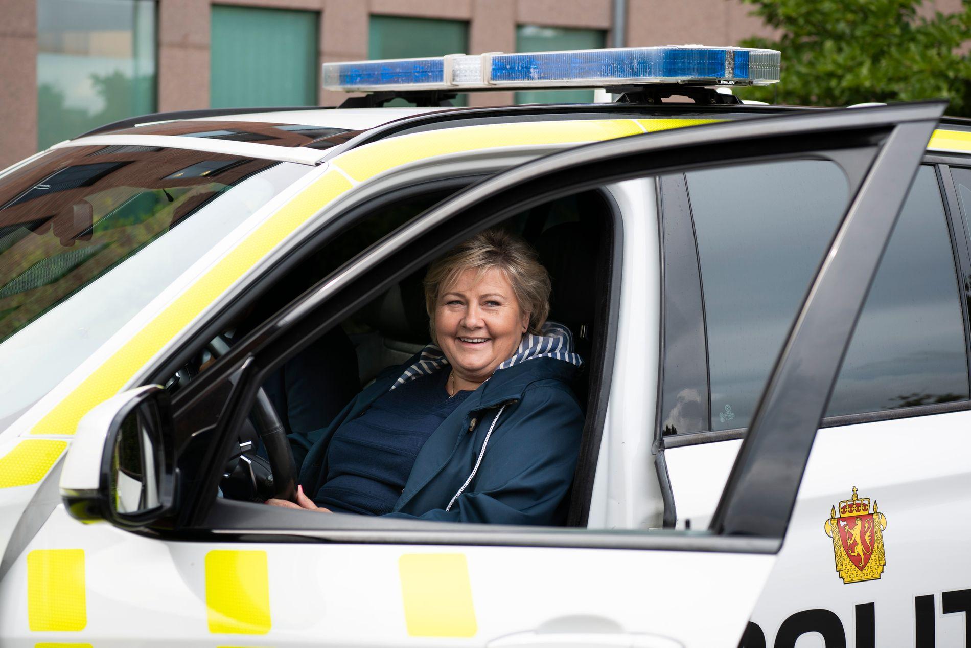 I FØRERSETET: Statsminister Erna Solberg i bak rattet i en politibil ved Lillestrøm politistasjon søndag.