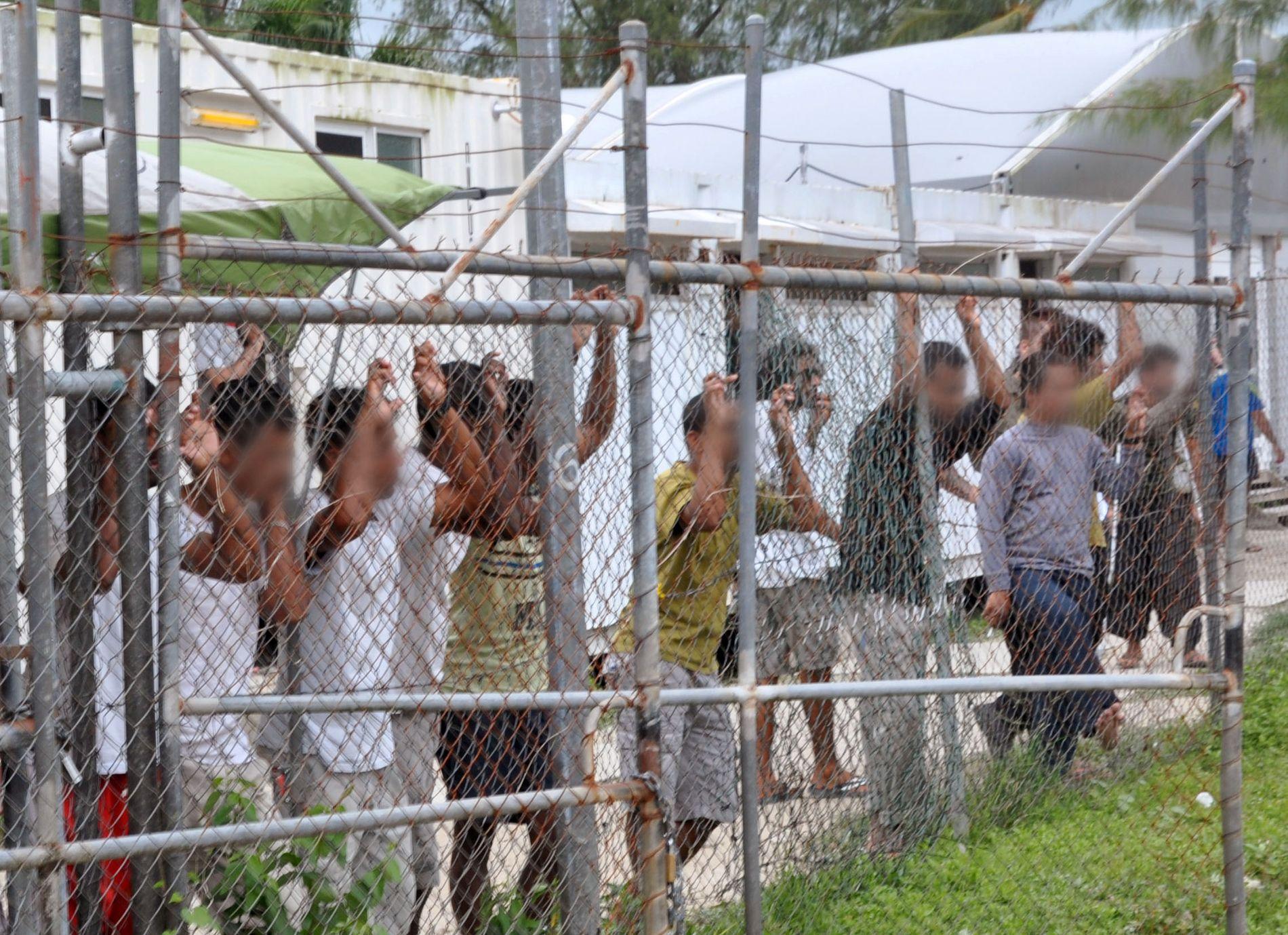 OVERGREP: Asylsøkere i en av Australias to leire utenfor eget territorium, titter ut gjennom gjerdet. Rapporter fra asylleiren på stillehavsøya Nauru avslører nå omfattende overgrep mot de som sitter internert der. FOTO: REUTERS