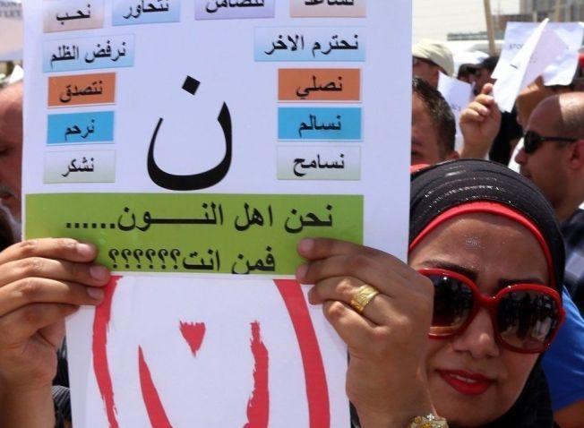 MERKET: En irakisk kvinne demonstrerer mot trusselen fra ISIL mot landets kristne. Hun bærer en plakat med det arabiske tegnet for kristne.