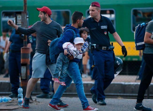 BARN: Det er mange barnefamilier i flyktningtoget. Denne mannen bærer to småbarn mens han geleides vekk av ungarsk politi.