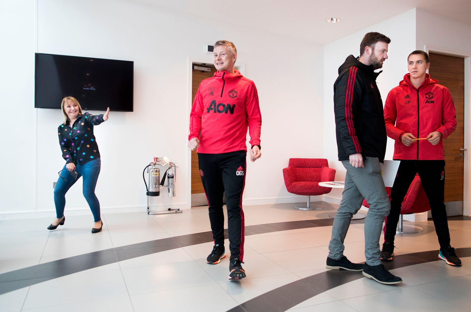 DIPLOM: Ole Gunnar Solskjær har slått av en spøk til pressesjefen Karen Shotbolt (t.v.) mens han kommer inn i resepsjonen på treningsfeltet Carrington. To andre United-ansatte til høyre.