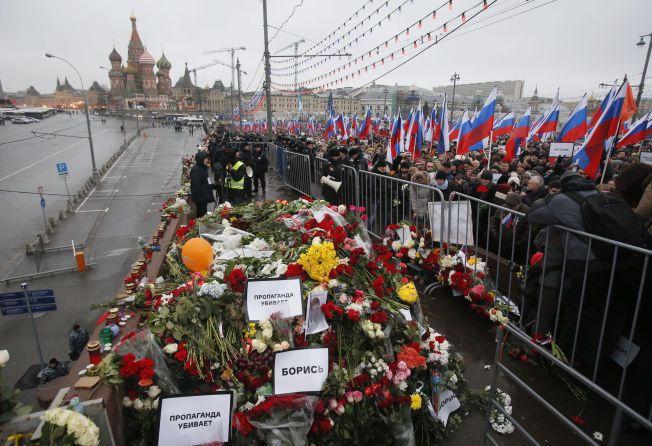 BLOMSTER OG FLAGG: Tusenvis av russiske flagg preger minnemarkeringen søndag. Siden drapet fredag har det vært fullt av blomster på plassen der Nemtsov ble funnet drept.